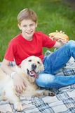 Leisure with dog. Portrait of cute lad and his fluffy friend on a picnic Royalty Free Stock Photos