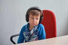 Leisure, education, children, technology and people concept - boy with computer and headphones at office royalty free stock image