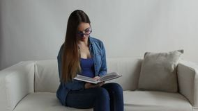 Woman sitting on couch reading book at home. Full HD. Leisure education and literature concept - Woman sitting on couch reading book at home. Full HD 1920X1080P stock video