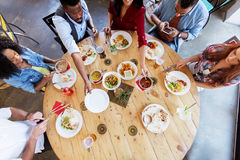Happy friends eating at restaurant. Leisure, food and people concept - group of happy international friends eating at restaurant table royalty free stock photo