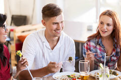 Happy friends eating and talking at restaurant. Leisure, food and people concept - group of happy international friends eating and talking at restaurant table stock image