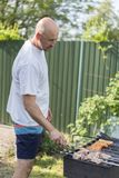 Leisure, food, people and holidays concept - happy young man cooking meat on barbecue grill at outdoor summer party.  Royalty Free Stock Photography