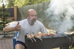 Leisure, food, people and holidays concept - happy young man cooking meat on barbecue grill at outdoor summer party.  Royalty Free Stock Images