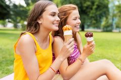 Teenage girls eating ice cream at picnic in park Stock Photos