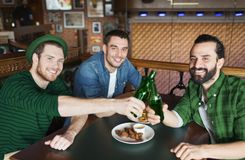 Friends drinking beer in bottles at bar or pub. Leisure, friendship and st patricks day celebration concept - happy male friends drinking beer and clinking Royalty Free Stock Photography