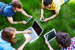 Leisure with gadgets. Group of friends with gadgets relaxing on green grass Royalty Free Stock Photos