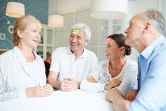 Leisure game. Group of friendly seniors playing leisure game of associations by table Stock Photo