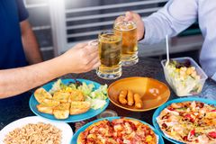 Leisure, holidays with beer grilled meat and vegetables served, Young People chatting and having drinks together enjoying outdoor royalty free stock images