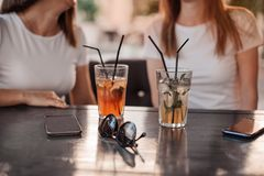 Leisure, holidays, eating, people and food concept - happy friends having dinner at summer garden party and clinking drinks stock photos