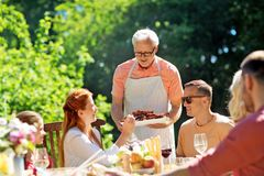 Family having dinner or barbecue at summer garden royalty free stock image