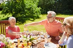 Happy family having dinner or summer garden party. Leisure, holidays and people concept - happy family having festive dinner or summer garden party Royalty Free Stock Photos