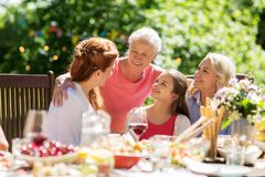 Happy family having dinner or summer garden party. Leisure, holidays and people concept - happy female family having festive dinner or summer garden party Stock Photo