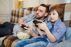 Leisure at home. Man and boy with popcorn sitting on couch and playing video games stock photos