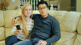 Leisure home. Young multi-ethnic family together watching television. Asian man and Caucasian woman stock video
