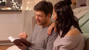 Happy couple reading book at home. Leisure, hygge and people concept - happy couple reading book at home stock footage