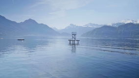 Leisure lake. Medium wide high dynamic range shallow depth of field handheld shot of a slide and diving board structure in a large lake surrounded by mountains stock video