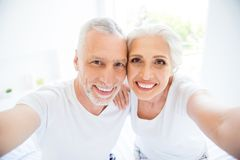 Leisure, lifestyle concept. Close up portrait of two carefree pe. Ople make selfie on the front of the smartphone in bright white room rest and relax on royalty free stock photos
