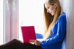 Woman sitting on window sill reading book at home. Leisure, literature and people concept. Young woman teen girl reading book at home while sitting on window stock photo