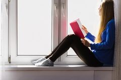 Woman sitting on window sill reading book at home. Leisure, literature and people concept. Young woman teen girl reading book at home while sitting on window royalty free stock photos