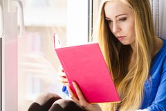 Woman sitting on window sill reading book at home. Leisure, literature and people concept. Young woman teen girl reading book at home while sitting on window stock images