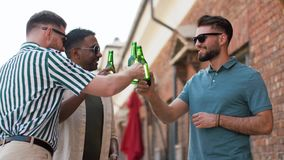 Happy male friends drinking beer at rooftop party. Leisure, male friendship and people concept - happy men or friends drinking beer at rooftop party in summer stock video