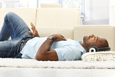 Leisure with music. Ethnic man lying on living room floor with headset, enjoying with closed eyes royalty free stock photography