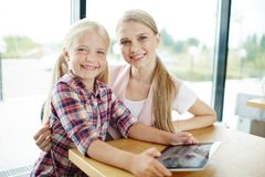 Leisure in the net. Pretty girl and her mother with touchpad enjoying leisure in the net Stock Images