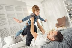 Inspired son and daddy playing together. Leisure. Nice content fair-haired boy smiling and having fun with his daddy while lying on his back on the sofa Royalty Free Stock Images