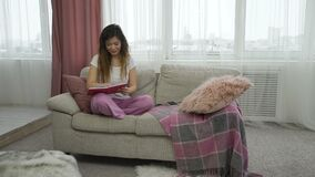 Leisure pastime casual teen girl relaxing diary. Leisure pastime. casual teenage girl relaxing time. young woman sitting on a sofa in comfortable home clothing stock video