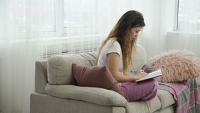 Leisure pastime casual teen girl reading diary. Leisure pastime. casual teenage girl sitting on a sofa in comfortable home clothing reading her diary stock video footage