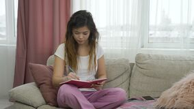 Leisure pastime teenage girl relax home writing. Leisure pastime. teenage girl having some me time. relaxed young woman sitting on a couch in comfortable home stock video footage