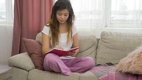 Leisure pastime teenage girl relax home writing. Leisure pastime. teenage girl having some me time. relaxed young women sitting on a couch in comfortable home Royalty Free Stock Images