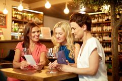 Women looking at bill at wine bar or restaurant. Leisure, payment and lifestyle concept - happy women with bill and wallet at restaurant or wine bar royalty free stock photos