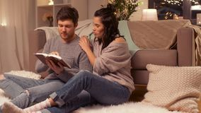 Happy couple reading book at home. Leisure and people concept - happy couple reading book at home stock video