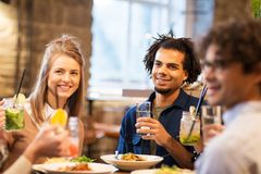 Happy friends eating at bar or restaurant. Leisure and people concept - happy friends eating and drinking non-alcoholic drinks at bar or restaurant stock images