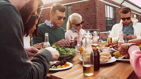 Friends having dinner or bbq party on rooftop. Leisure and people concept - happy friends having dinner or bbq party and eating on rooftop in summer stock video footage
