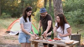 Leisure and people concept - happy friends toasts, drinks, summer party in the forest with tent at sunset. stock video