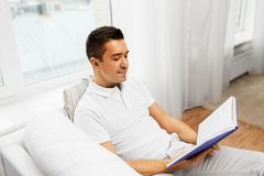 Happy man reading book at home royalty free stock photos