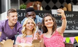 Happy young friends taking selfie at food truck stock image