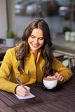 Happy woman with notebook drinking cocoa at cafe royalty free stock photos
