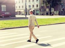Senior man walking along city crosswalk stock photo