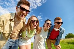 Happy teenage friends laughing outdoors in summer stock photography
