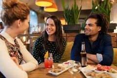 Happy friends with drinks and food at bar or cafe Stock Photography
