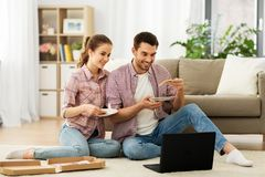 Happy couple with laptop eating pizza at home stock photos