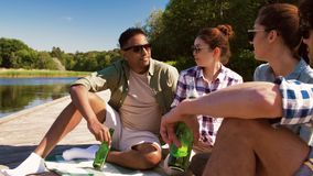 Friends with drinks on wooden pier at lake. Leisure, picnic and people concept - friends drinking beer and cider on wooden pier at lake or river stock video