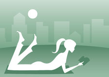 Leisure Reading. Silhouette of a girl lying in the grass with a good book, a cityscape in the background Royalty Free Illustration