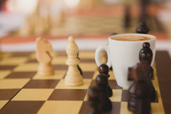 Leisure relax time or business strategy concept. Part of chess table with coffee cup Royalty Free Stock Images