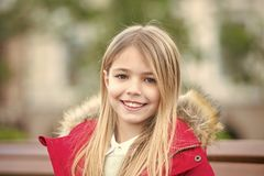Leisure, relaxation, lifestyle. Girl in red coat sit on bench in park. Child with blond long hair smile outdoor. Kid enjoy autumn day. Happy childhood concept royalty free stock images