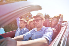 Leisure, road trip, travel and people concept - happy friends driving in cabriolet car along country road.  Royalty Free Stock Photos
