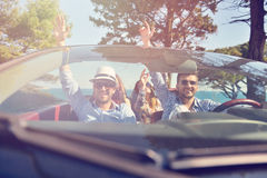 Leisure, road trip, travel and people concept - happy friends driving in cabriolet car along country road Royalty Free Stock Photos